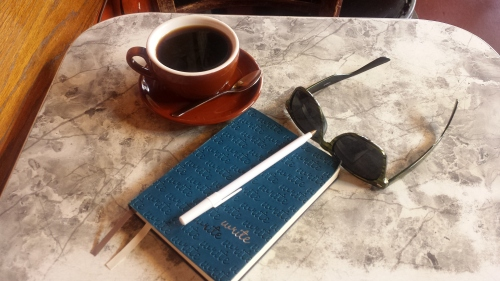 Coffee, journal, sunglasses.