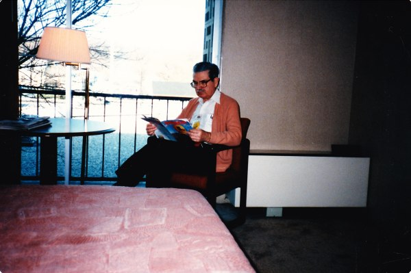 Grandfather reading a magazine in a hotel