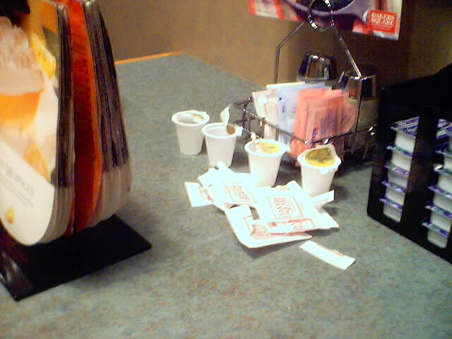 Empty sugar packets and coffee creamer