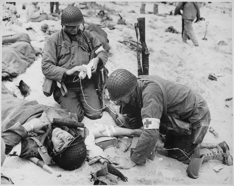 Medics_helping_injured_soldier_in_France,_1944